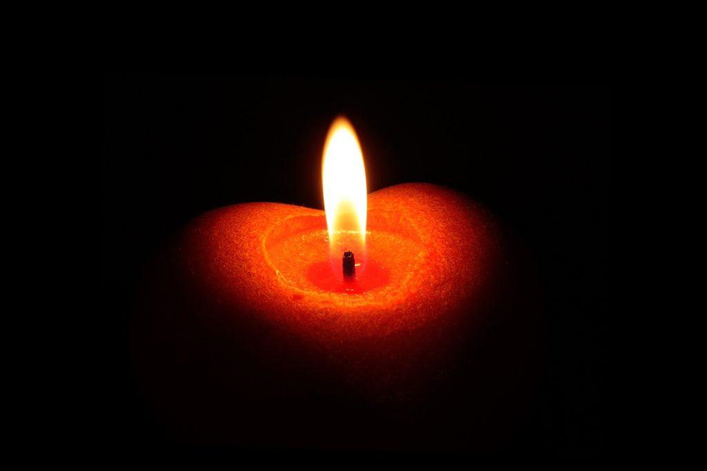 Brennende rote Kerze in Herzform vor schwarzem Hintergrund.